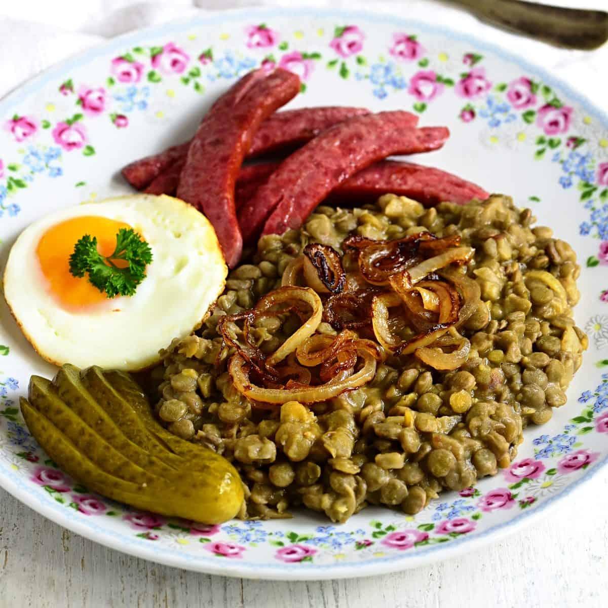 Saure Linsen - tschechische čočka na kyselo serviert mit Ei, eingelegter Gurke und Wurst.